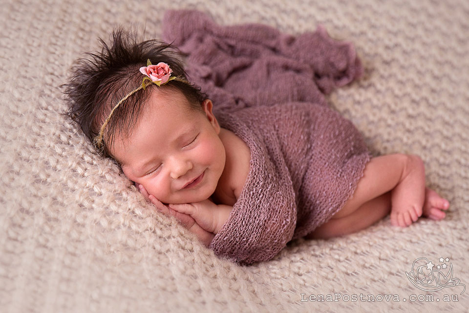 Newborn Session Sydney - Baby photographer Lena Postnova. New baby posed on her side wrapped in the dusty pink wrap.