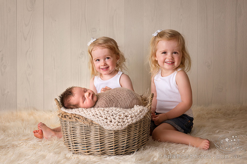 Baby Photographer Sydney - smiling twin 2 years old with the newborn brother sleeping in the basket